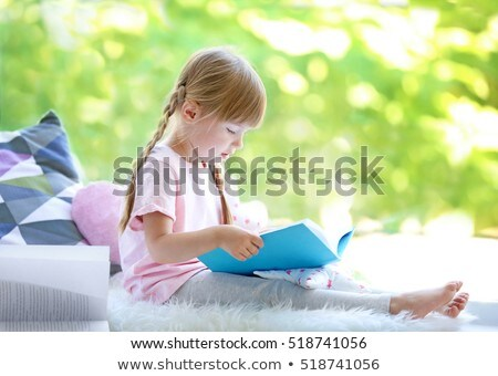 Cute little girl reading book at home, at windowsill Stock photo © Illia