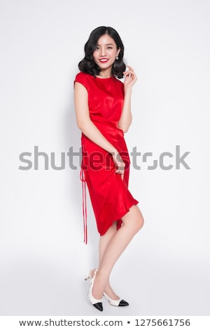 portrait of a smiling asian woman in dress standing stock photo © deandrobot