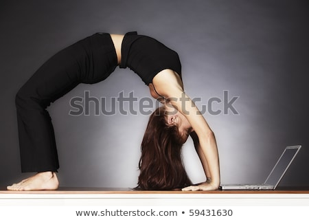 woman in yoga wheel pose looking at laptop stock photo © lichtmeister