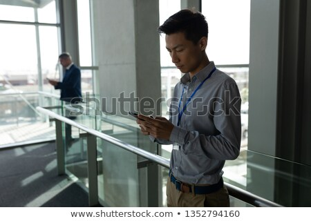 side view of asian focus businessman using his mobile phone on the first floor walkway of office aga stock photo © wavebreak_media