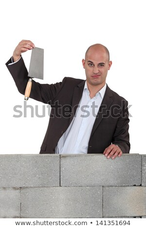 Office worker stood with trowel next to wall Stock photo © photography33
