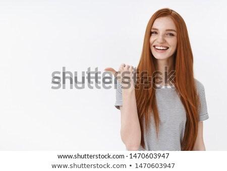 uśmiechnięty · młoda · kobieta · wskazując · patrząc · biały · kobieta - zdjęcia stock © stockyimages