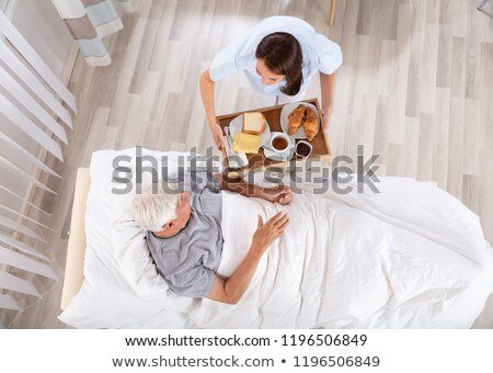 Foto stock: Nurse Serving Food To Senior Male Patient In Clinic