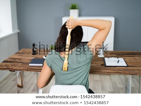 Woman Using Back Scratcher Stock photo © AndreyPopov