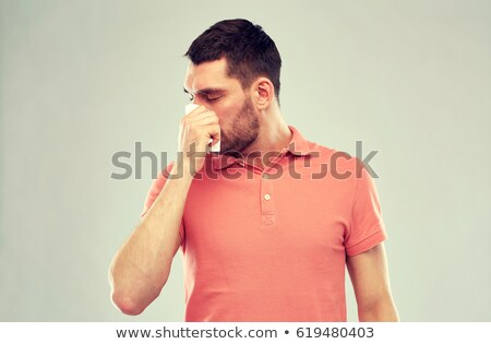 unhealthy man with paper napkin blowing nose Stock photo © dolgachov