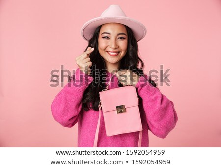 Image of asian girl in hat showing money counting gesture and ho Stock photo © deandrobot