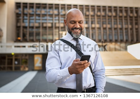 senior man texting message on smartphone in city Stock photo © dolgachov