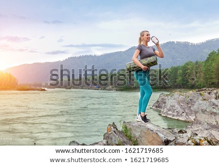 Beautiful blond girl stands near the river Stock photo © Nejron