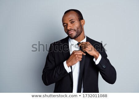African man adjusting his necktie over white background Stock photo © deandrobot