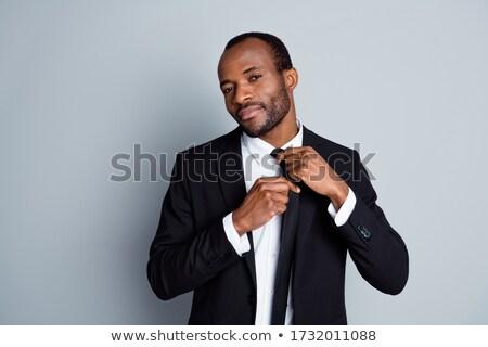 african man adjusting his necktie over white background stock photo © deandrobot