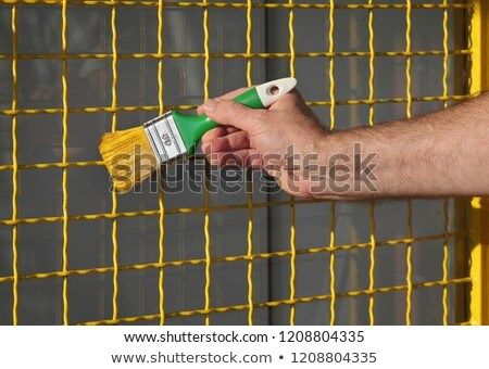 Stock photo: Worker painting metal protective net to yellow color