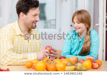 Father cutting apple with knife for his daughter Stock photo © Kzenon