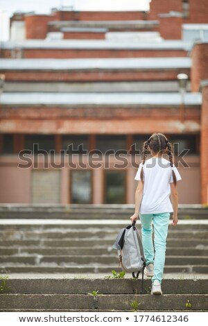 Rear view of a schoolgirl sitting with her friends in classroom at school Stock photo © wavebreak_media