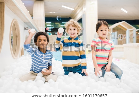 Group of adorable little children in casualwear playing with white balloons Stock photo © pressmaster