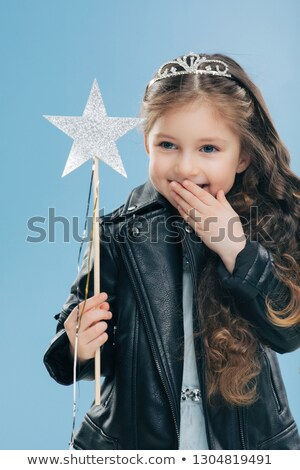 Glad pleasant looking small kid covers mouth with palm, giggles positively, wears crown and black le Stock photo © vkstudio