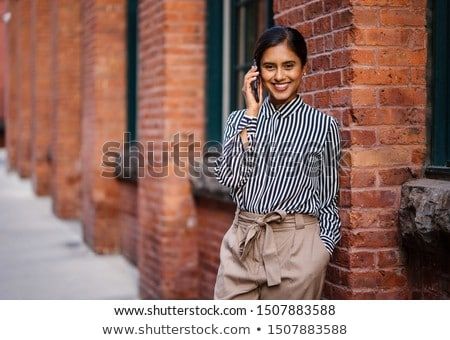 Businesswoman talking on her mobile phone and leaning against a blank sign Stock photo © photography33