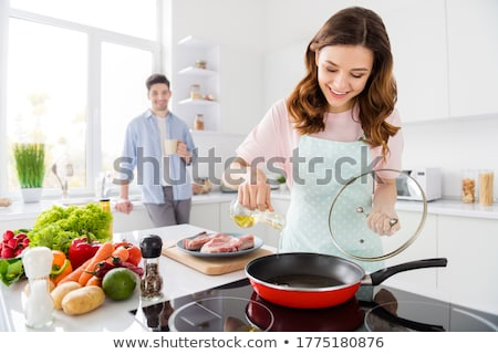 Portrait of a woman holding a cup of coffee in her kitchen stock photo © wavebreak_media