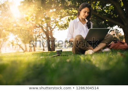 Woman sitting outdoors in park using laptop computer listening music with earphones. Stock photo © deandrobot