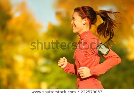 Young sports woman in park outdoors listening music with earphones looking at watch. Stock photo © deandrobot
