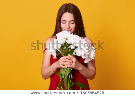 beautiful girl being happy smelling a yellow blossom stock photo © lichtmeister