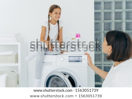 Housewife and small child sit on top of washing machine, holds freshly washed towels, do washing tog Stock photo © vkstudio