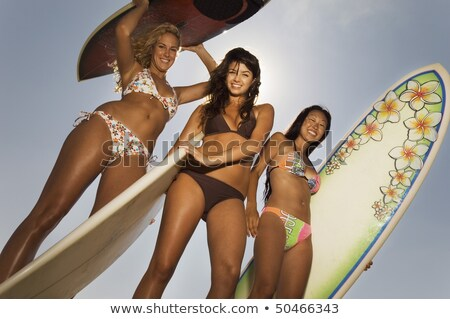 Low angle view of beautiful Caucasian female surfer holding surfboard at beach. She is shielding her Stock photo © wavebreak_media