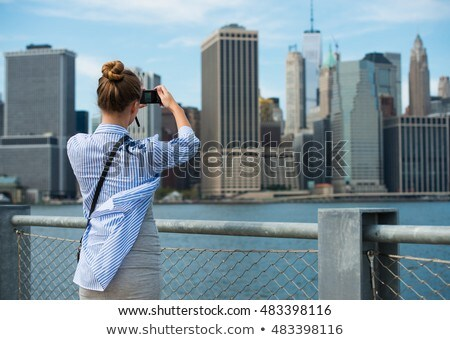 Tourist woman taking travel picture of New York City skyline wit Stock photo © boggy