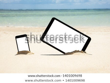 Mobile Phone And Digital Tablet Dig On Sand At Beach Stock photo © AndreyPopov