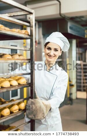 Baker donna spingendo pane cottura forno Foto d'archivio © Kzenon