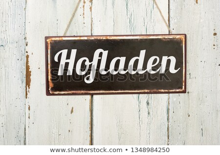Old metal sign in front of a white wooden wall - Farm Shop Stock photo © Zerbor