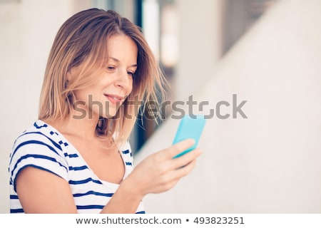 Portrait of cute young woman using smartphone outside. Stock photo © deandrobot