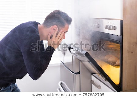 Young Man Looking At Smoke Coming From Oven Stock photo © AndreyPopov