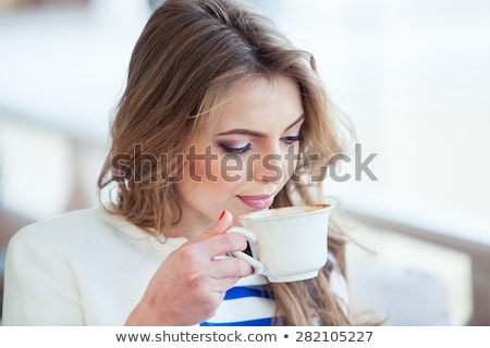 Stockfoto: Positive girl drinking coffee at cafeteria.