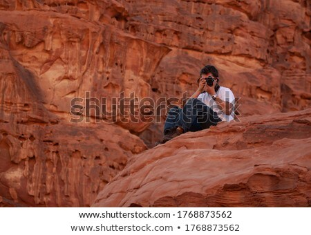 photo of european beautiful man in white t shirt sitting on gras stock photo © deandrobot