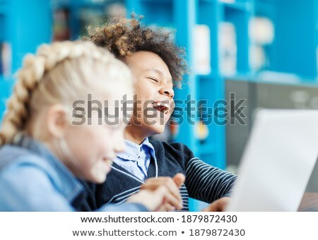 Vista lateral feliz colegiala usando la computadora portátil mirando cámara Foto stock © wavebreak_media
