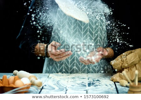 The man, chef cooks throws the dough, flying, freezing in motion. Stock photo © Illia