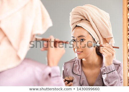 Woman applying clay mask with brush at home Stock photo © Elnur