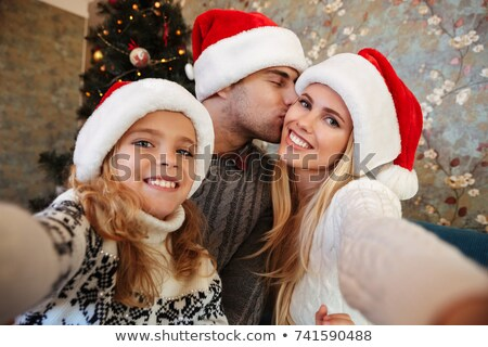Little blonde daughter in Santa's hat taking selfie while her pa Stock photo © deandrobot