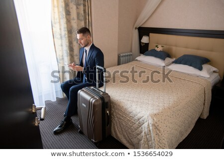 Business traveler in suit scrolling in smartphone while going to call taxi Stock photo © pressmaster