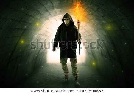 Man walking with burning flambeau in a dark tunnel Stock photo © ra2studio