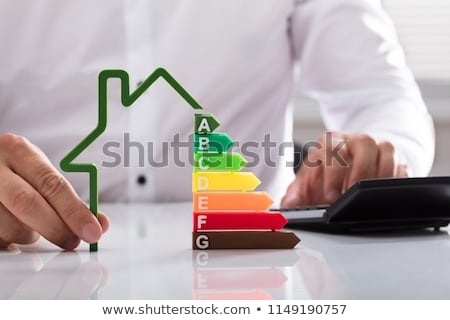 Person Holding Green House Energy Efficiency Graph Stock photo © AndreyPopov