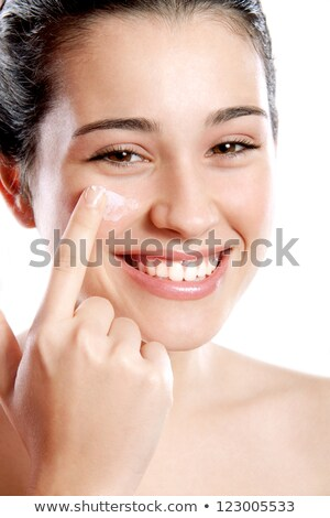 Young cheerful woman with toothy smile pampering cream on her face Stock photo © pressmaster