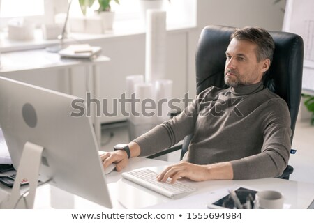Serious manager concentrating on work while sitting in front of computer screen Stock photo © pressmaster