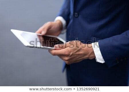 Mid section of elegant mixed-race businessman using digital tablet standing in modern office Stock photo © wavebreak_media