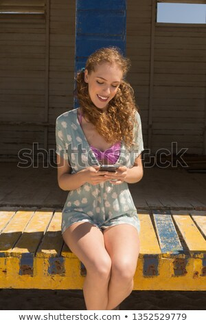 Front view of happy gorgeous young woman using mobile phone sitting on beach hut. She is smiling Stock photo © wavebreak_media