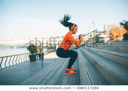 Image of fitness woman in sportswear listening to music with headphones Stock photo © deandrobot