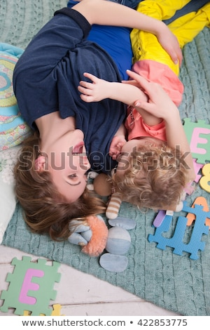 Playful young woman lying on her back on a carpet Stock photo © Giulio_Fornasar