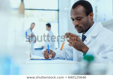 Scientist or medical in lab coat holding test tube with reagent, Stock photo © Freedomz