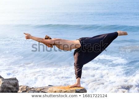 Homem ioga guerreiro pose praia ao ar livre Foto stock © dmitry_rukhlenko
