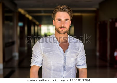 Portrait of young man inside shopping mall standing relaxed and  Stock photo © HASLOO